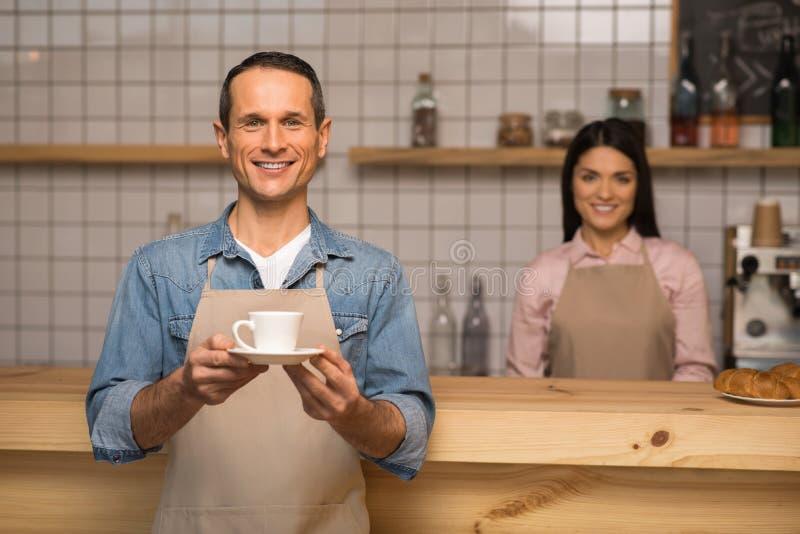 Garçom que guarda a xícara de café imagem de stock