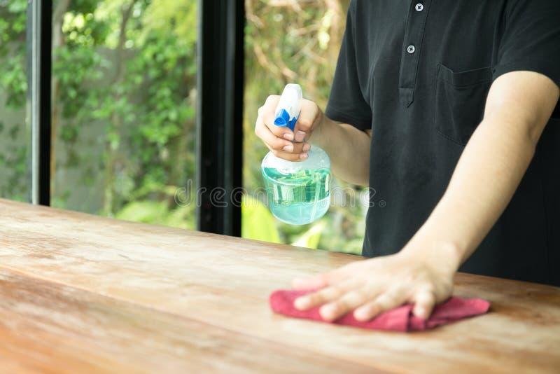 Garçom que limpa a tabela com o desinfetante do pulverizador imagem de stock