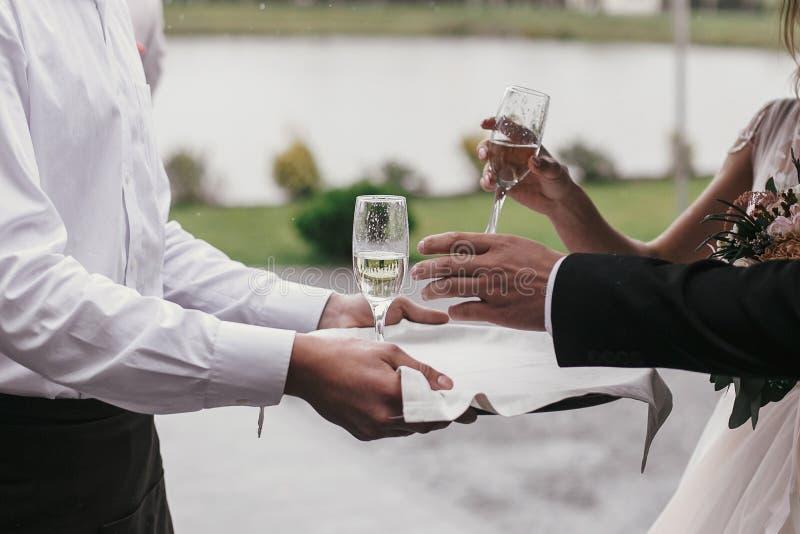 Garçom que serve o champanhe ao grupo de pessoas Mãos que brindam com fotos de stock royalty free