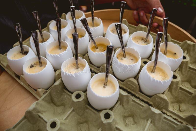 Garçom que serve ovos no copo de ovo com colher pequena fotografia de stock royalty free