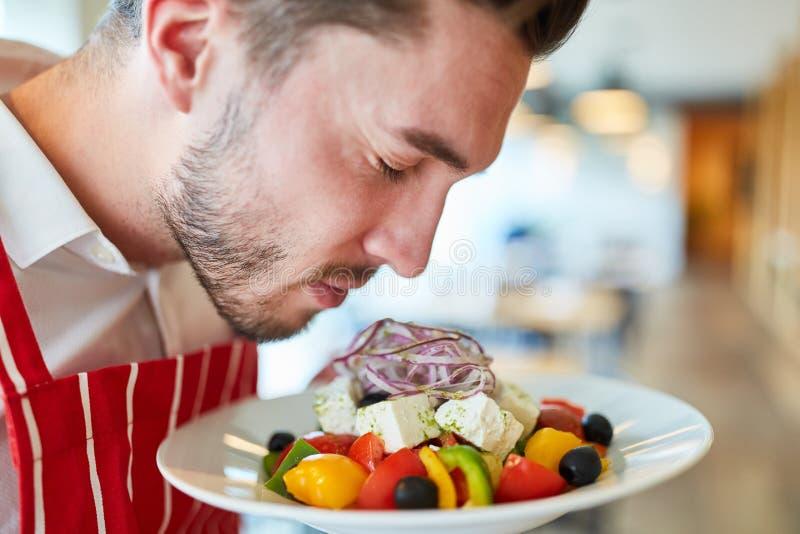 Garçom que serve a salada grega fresca fotografia de stock