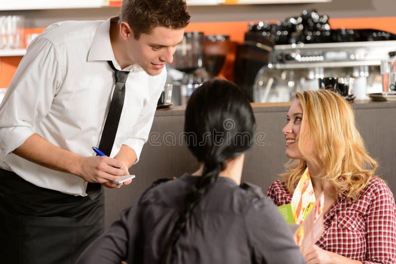 Garçom que toma ordens do cliente da jovem mulher fotografia de stock royalty free