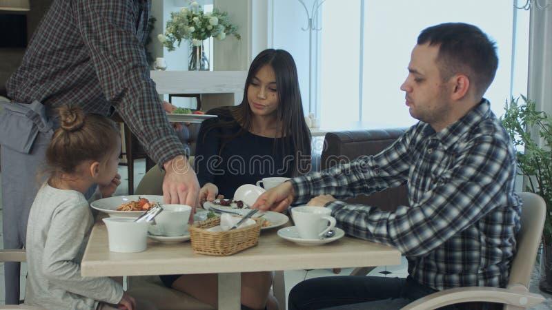 Garçom que traz a massa à menina bonita pequena que tem o jantar com sua família no restaurante Os pais têm comeu o seu fotos de stock royalty free