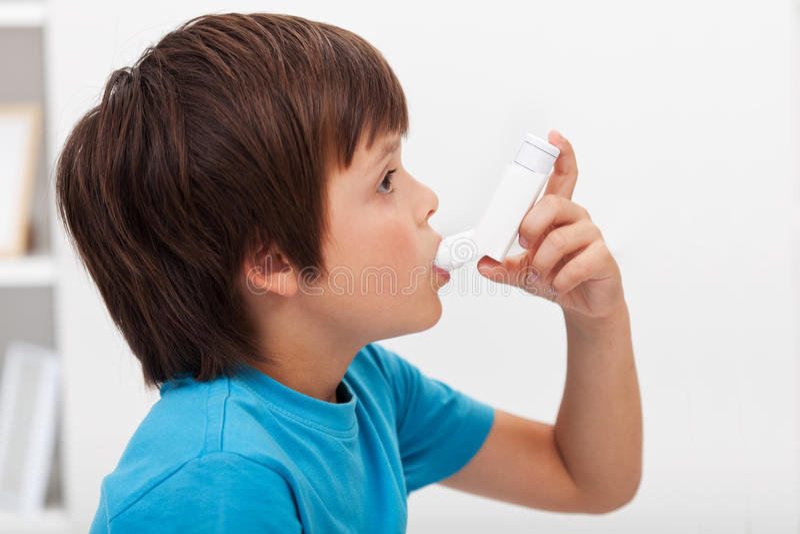 Garçon à l'aide de l'inhalateur photographie stock libre de droits
