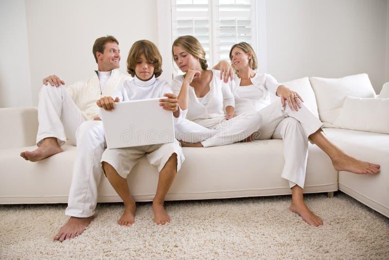 Garçon à l'aide de l'ordinateur portatif se reposant avec la famille sur le sofa blanc photos stock