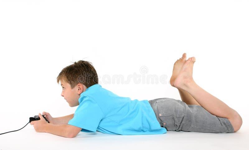 Garçon à l'aide de la console jouant des jeux photographie stock