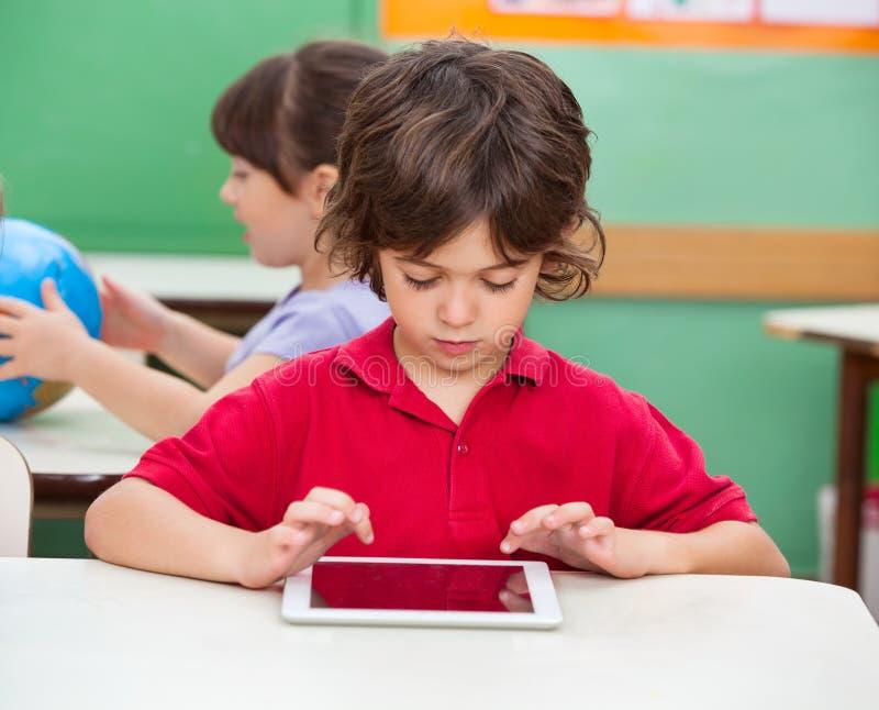 Garçon à l'aide de la Tablette de Digital au bureau image libre de droits