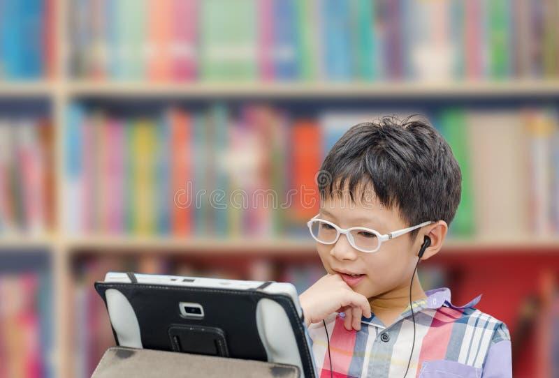 Garçon à l'aide de la tablette et de l'écouteur photos libres de droits