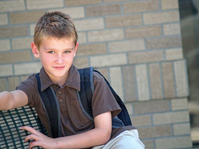Garçon à l'arrêt d'autobus scolaire images libres de droits