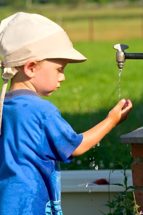 Garçon à l'eau du robinet image stock