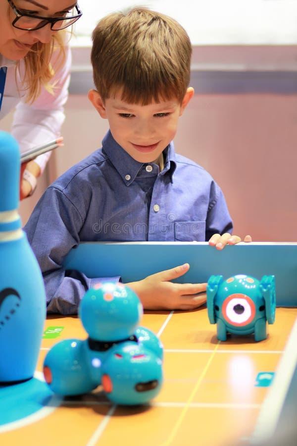 Garçon à la leçon de robotique Le professeur montre atelier à tout neuf de merveille le tiret intelligent de robot cheminée photographie stock libre de droits