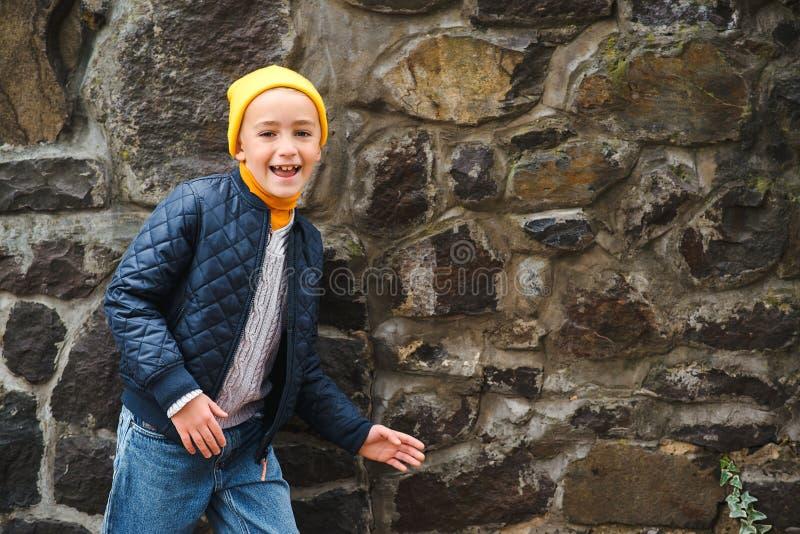Garçon à la mode mignon près du mur en pierre Concept de mode d'enfants Enfant drôle regardant à la caméra et au sourire Garçon à image stock
