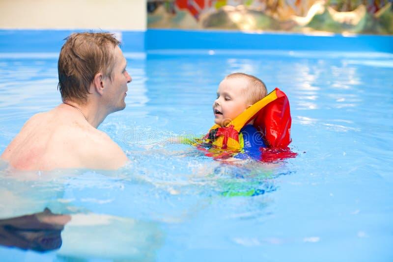 Garçon à nager dans la piscine avec le père photos stock