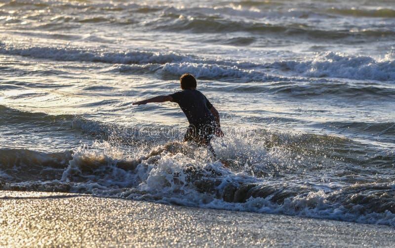 Garçon éclaboussant l'eau et ayant l'amusement sur la plage tropicale pendant la vue scénique de coucher du soleil de vacances de photographie stock