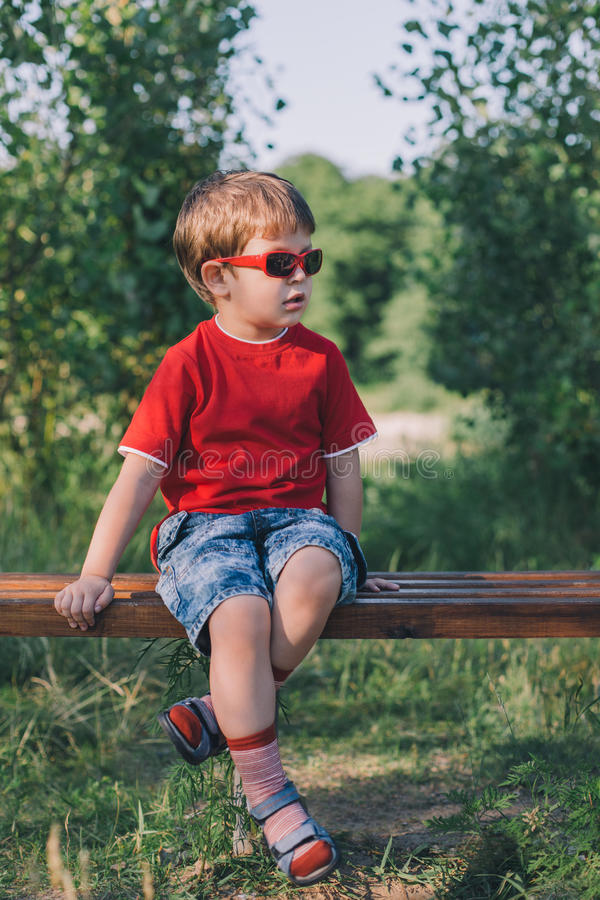 Garçon élégant dans des lunettes de soleil se reposant sur le banc images libres de droits