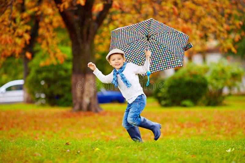 Garçon élégant heureux avec le parapluie fonctionnant en parc images libres de droits