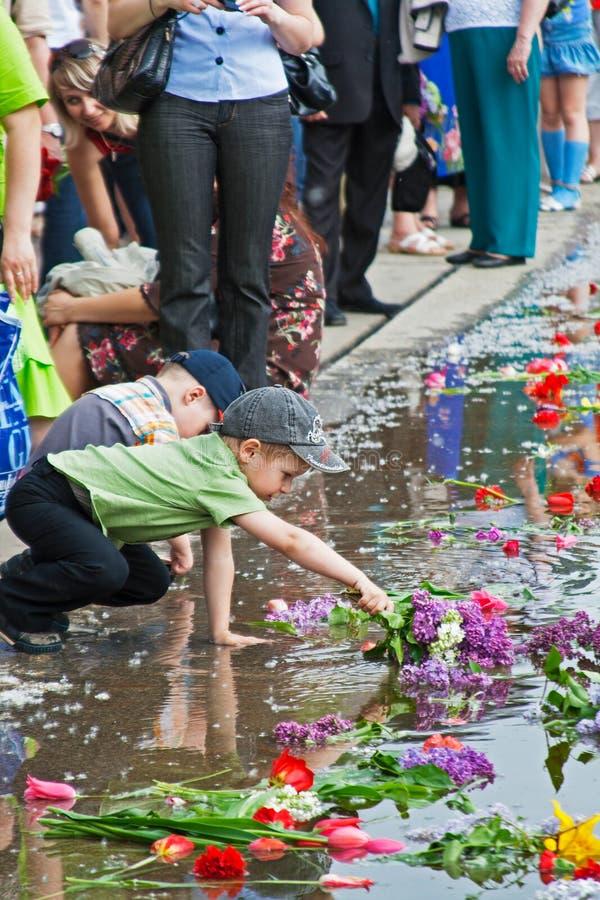 Garçon étendant des fleurs sur un lac des larmes sur Mamaev Kurgan à Volgograd photos libres de droits