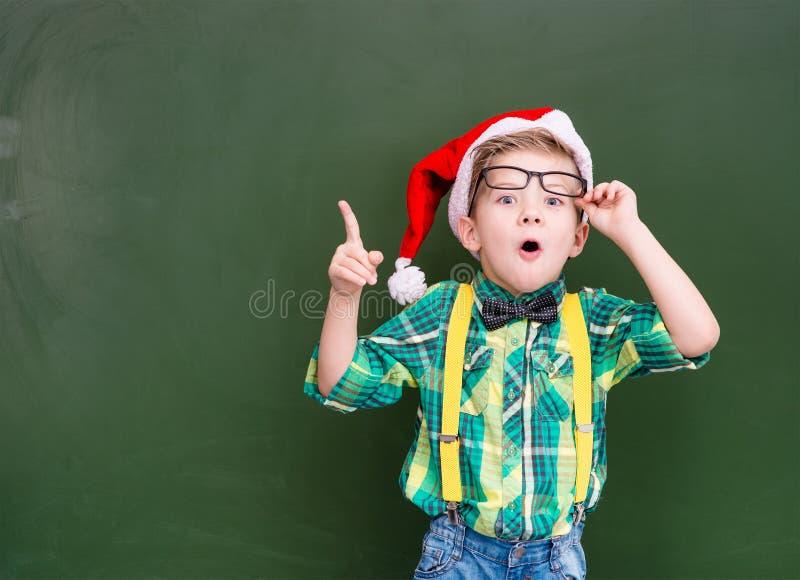 garçon étonné dans le chapeau rouge de Noël près d'un showi vert de tableau photos stock