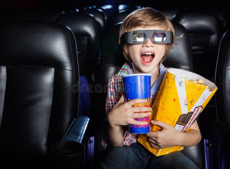 Garçon étonné observant le film 3D dans le théâtre photographie stock