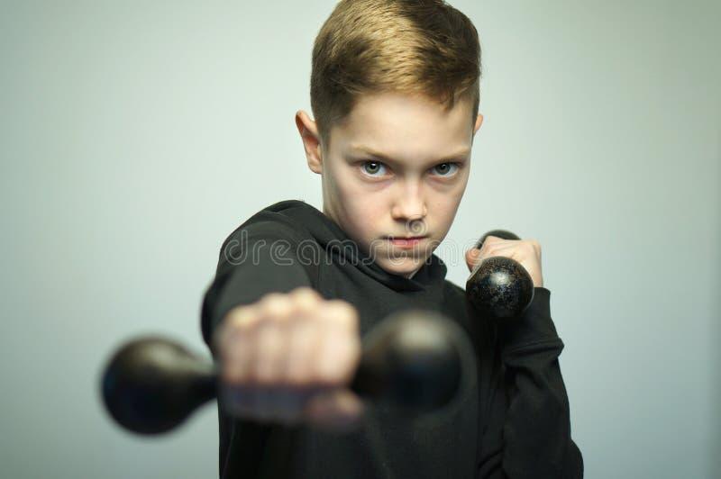Garçon adolescent de sport avec des haltères et la coupe de cheveux élégante, tir de studio image libre de droits