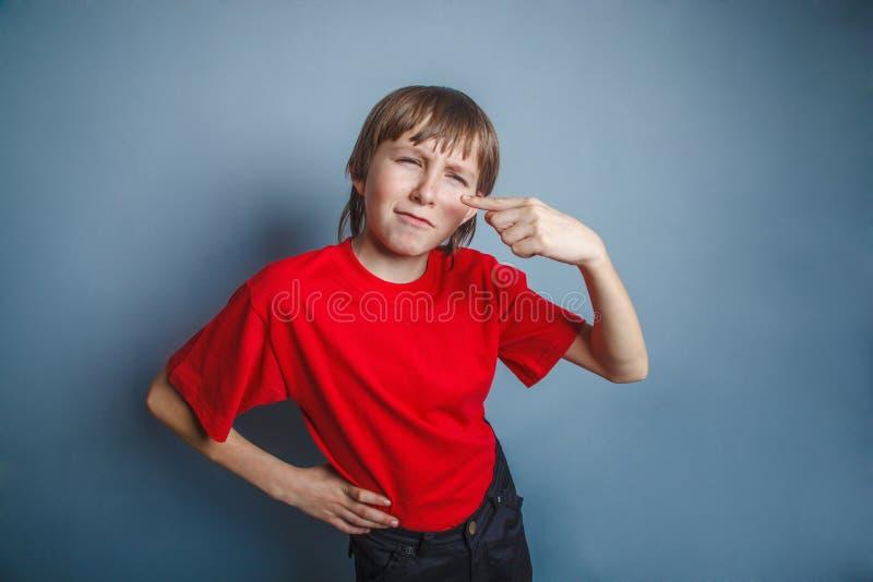 Garçon, adolescent, douze ans dans la chemise rouge, nez image stock