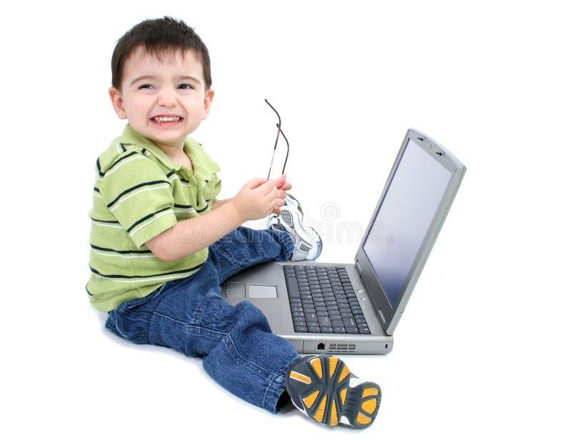 Garçon adorable avec le fonctionnement en verre sur l'ordinateur portatif au-dessus du blanc photo libre de droits