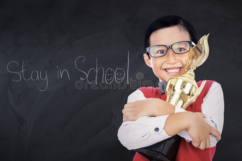 Garçon adorable avec le trophée dans la classe photographie stock libre de droits