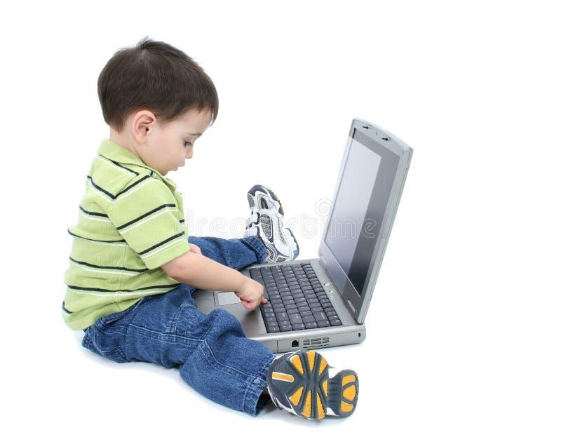 Garçon adorable avec travailler sur l'ordinateur portatif au-dessus du blanc photo stock