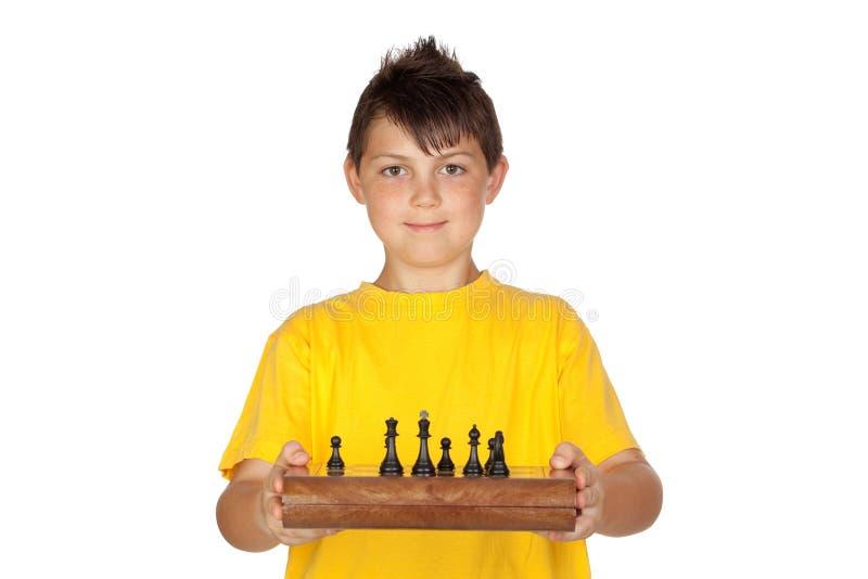 Garçon adorable avec un jeu d'échecs photo stock