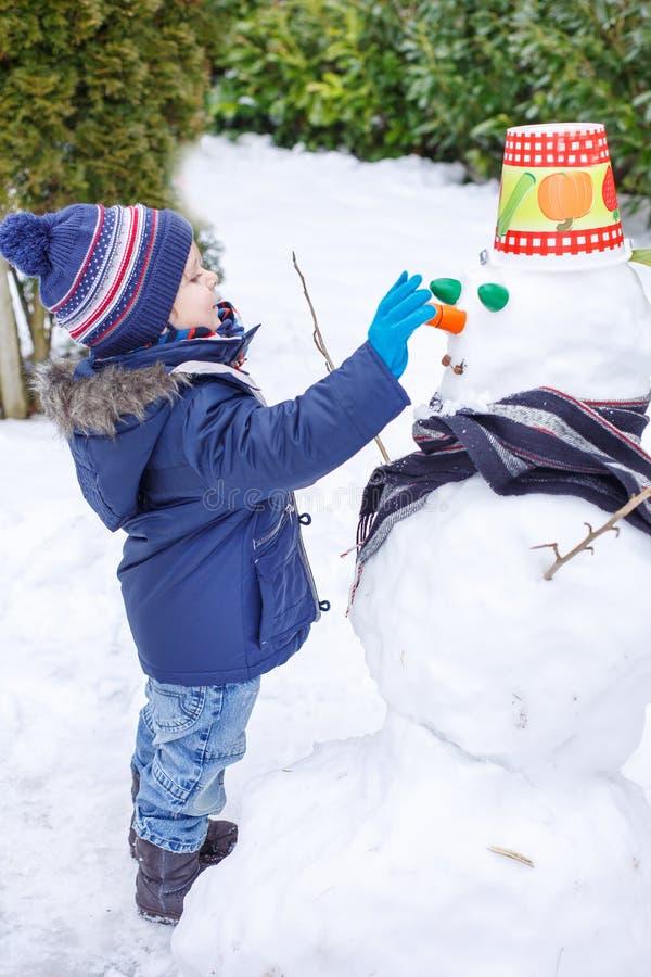 Garçon adorable d'enfant en bas âge ayant l'amusement avec le bonhomme de neige le jour d'hiver images stock