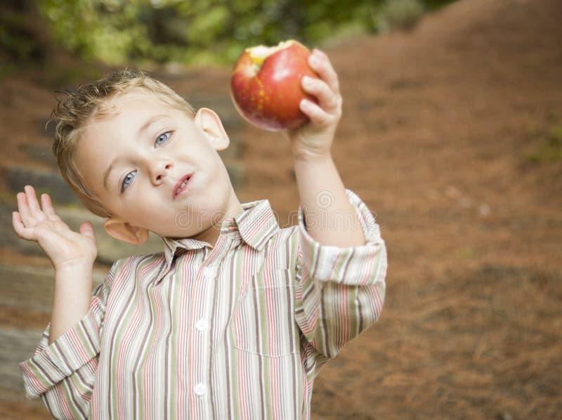 Garçon adorable d'enfant mangeant Apple rouge dehors photographie stock libre de droits