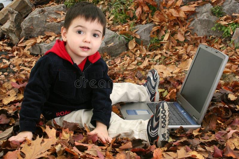 Garçon adorable dans des lames avec l'ordinateur portatif photo libre de droits