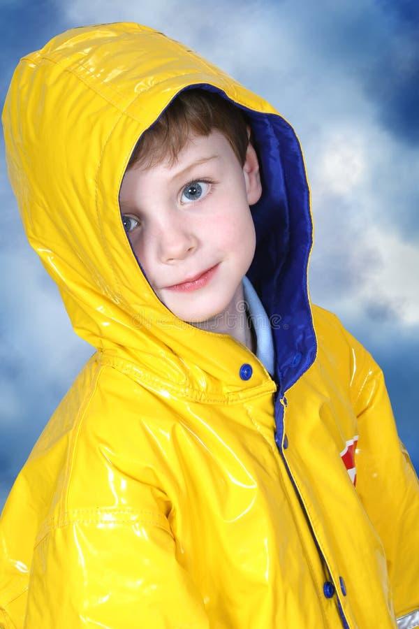 Garçon adorable de quatre ans dans la couche de pluie photographie stock libre de droits