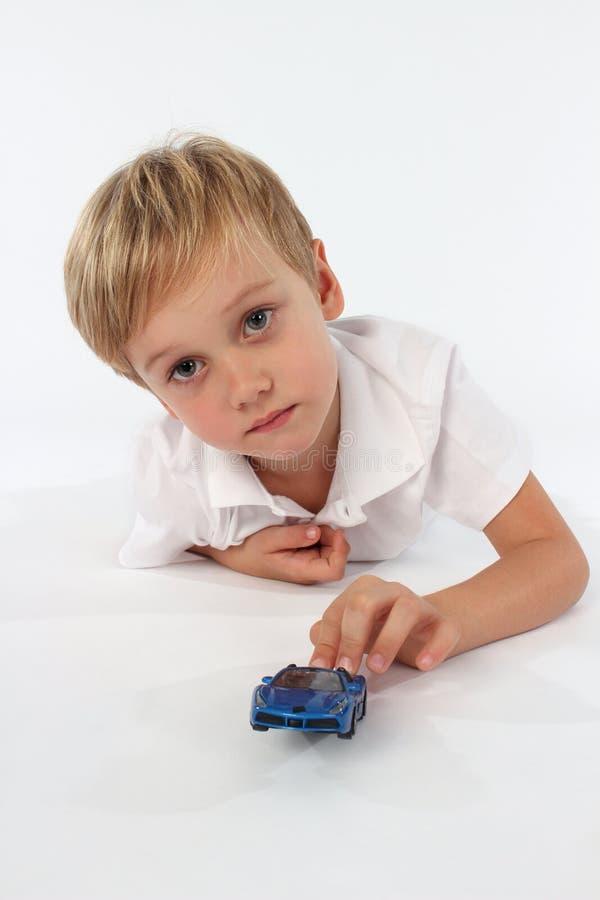 Garçon adorable jouant avec son jouet préféré de voiture image libre de droits