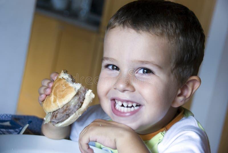 Garçon adorable mangeant le cheeseburger photo libre de droits