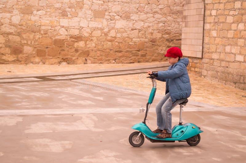 Garçon adorable montant le scooter électrique photographie stock