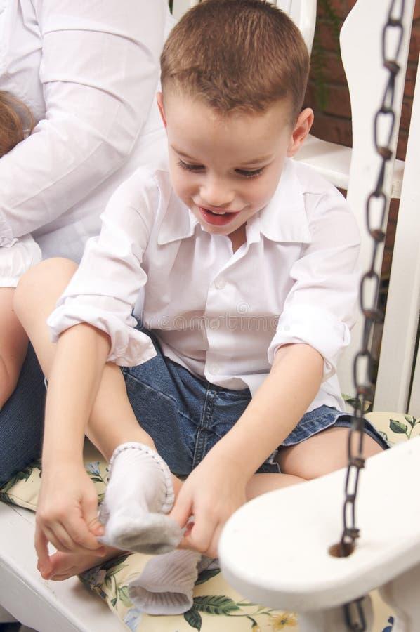 garçon adorable obtenant des chaussettes jeunes photographie stock libre de droits