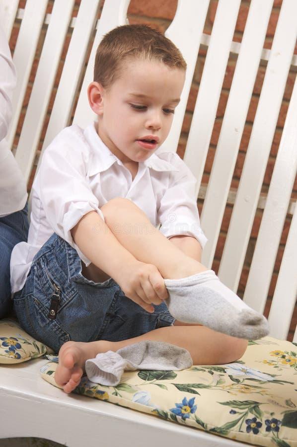 garçon adorable obtenant des chaussettes jeunes image stock