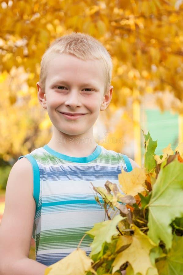 Garçon adorable souriant et tenant des feuilles d'automne image stock