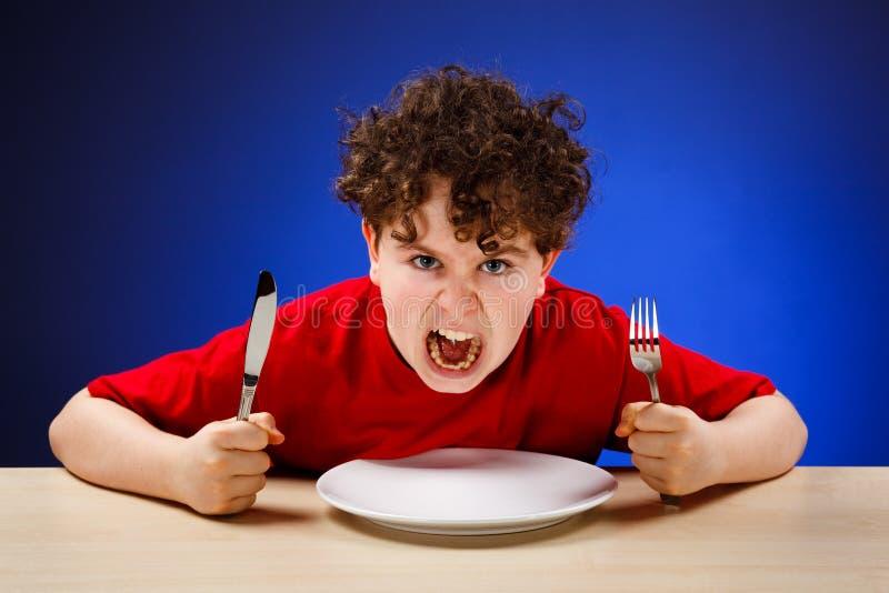 Garçon affamé photos stock