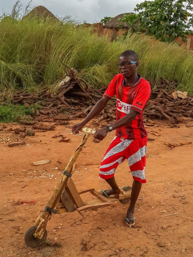 Garçon africain local avec le remplaçant angolais rouge lumineux de chemise du football image stock