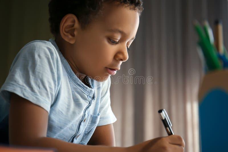 Garçon afro-américain mignon faisant ses leçons à la maison photos stock