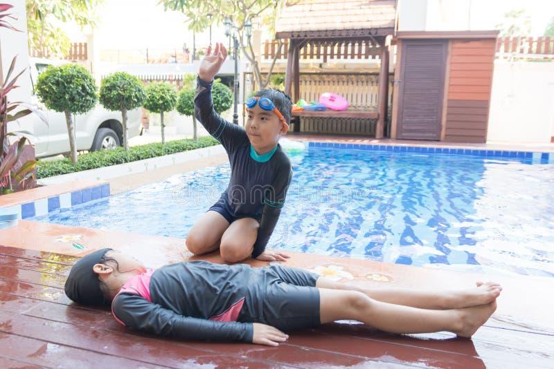 Garçon aidant noyant la fille d'enfant dans la piscine en faisant le CPR images stock