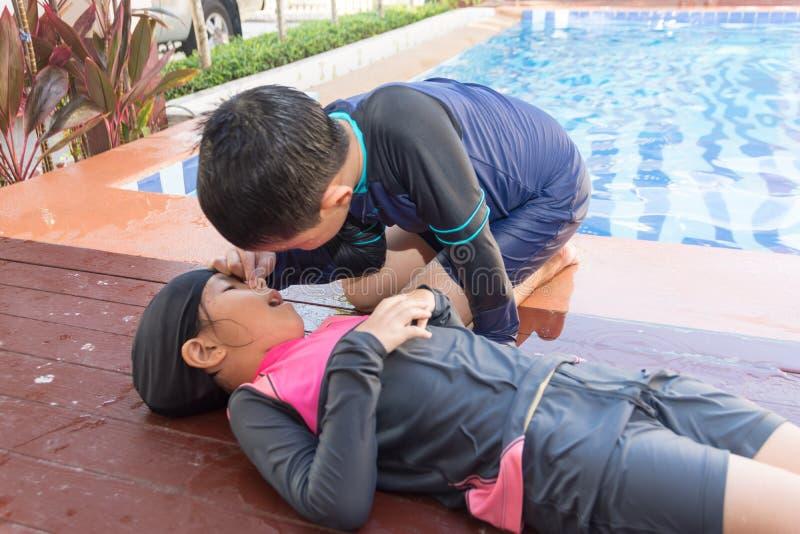 Garçon aidant noyant la fille d'enfant dans la piscine en faisant le CPR images libres de droits