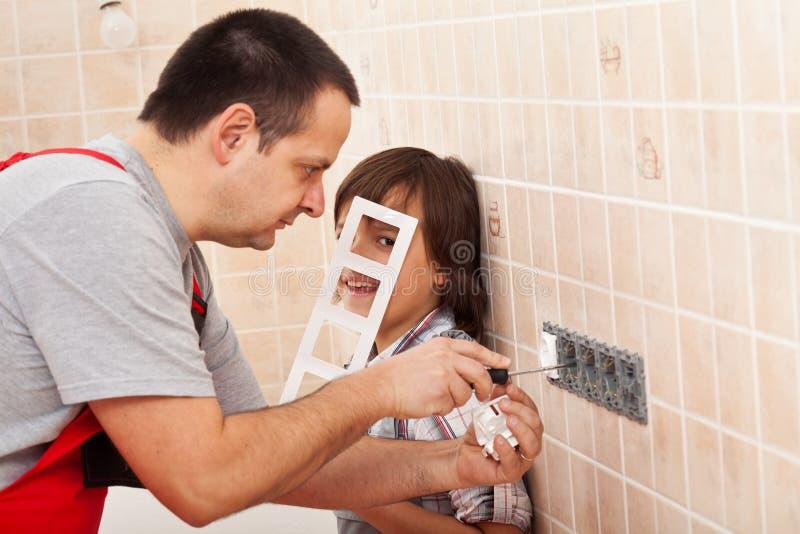 Garçon aidant son père dans le travail d'électricien photographie stock