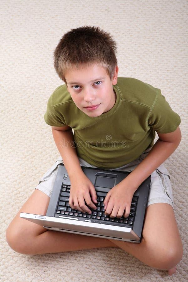 Garçon apprenant à la maison avec le cahier images stock