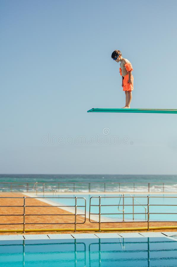 Garçon apprenant à plonger à la piscine photographie stock