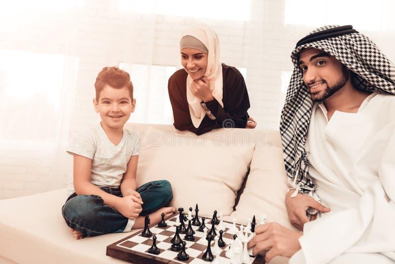 Garçon Arabe jouant aux échecs avec le père à la maison photographie stock