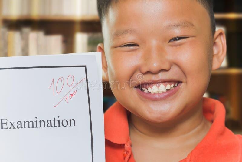Garçon asiatique avec des feuilles d'examen de plein score photographie stock libre de droits