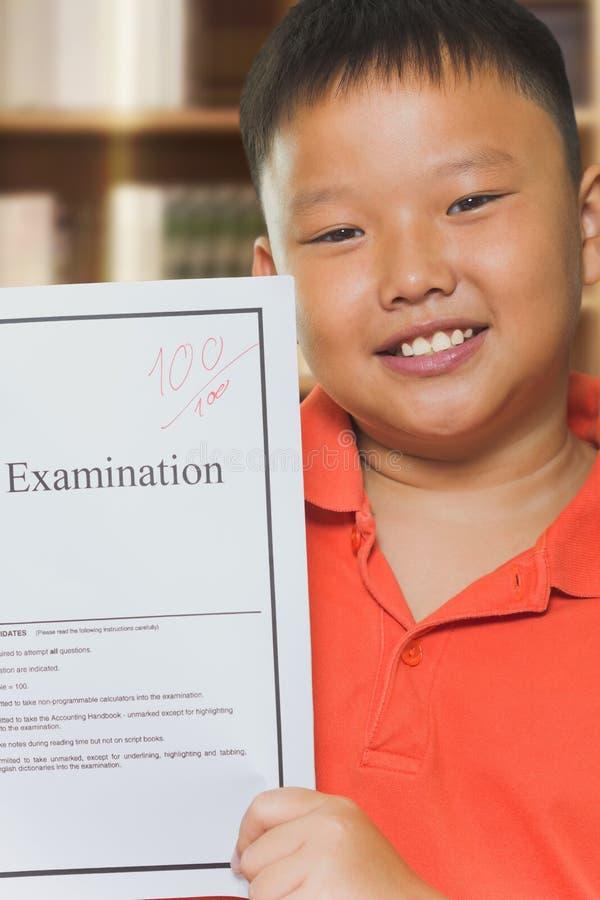 Garçon asiatique avec des feuilles d'examen de plein score photo libre de droits
